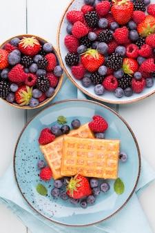 Salada de frutas frescas em um prato sobre um fundo de madeira. camada plana, vista superior, espaço de cópia.