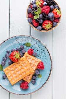 Salada de frutas frescas em um prato sobre uma superfície de madeira. camada plana, vista superior, espaço de cópia.