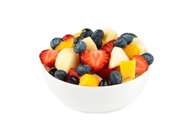 Salada de frutas frescas em uma tigela branca isolada no fundo branco