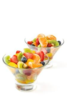 Salada de frutas frescas na tigela de cristal isolada no branco