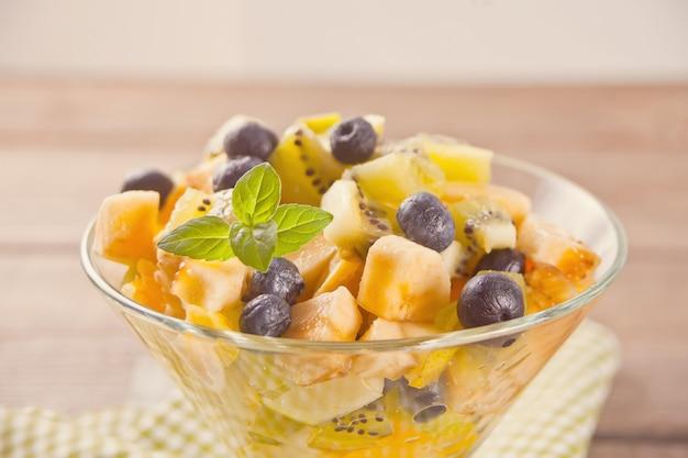Salada de frutas frescas na tigela sobre a mesa de madeira
