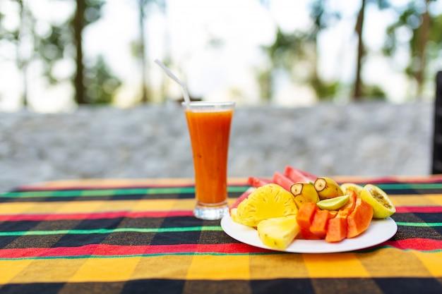 Salada de frutas. frutas frescas e suculentas em um prato em um fundo de montanhas
