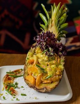 Salada de frutas mista servida dentro de abacaxi esculpido com ervas.