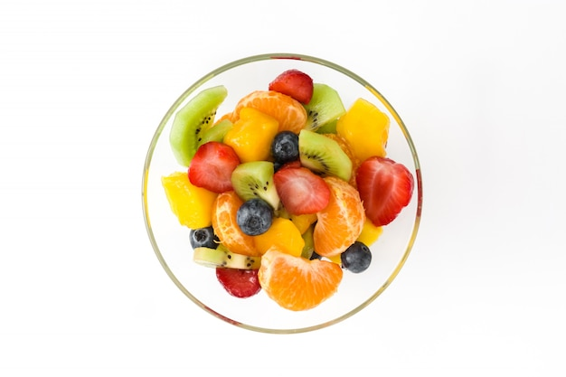 Salada de frutas na tigela de cristal isolada no branco, vista superior
