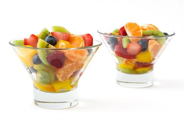 Salada de frutas na tigela de cristal isolada no branco