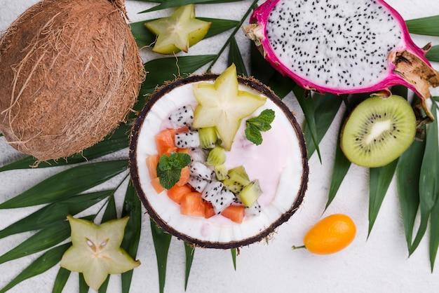 Salada de frutas no prato de coco e iogurte