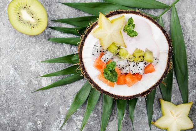 Salada de frutas no prato de coco e metade do kiwi