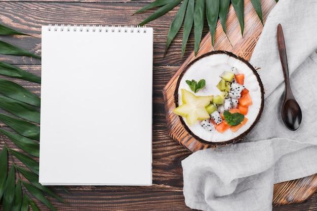 Salada de frutas no prato de coco e o bloco de notas vazio