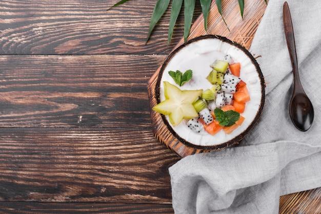 Salada de frutas no prato de coco na mesa de madeira