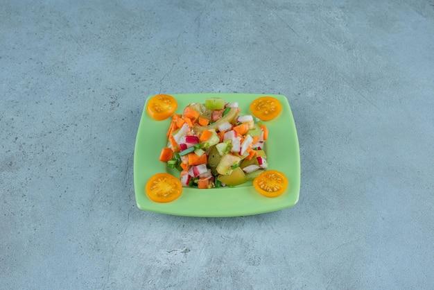 Salada de frutas picadas em um prato de cerâmica no concreto.