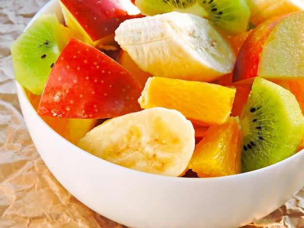 Salada de frutas suculenta fresca em uma tigela branca sobre um fundo de papel amassado