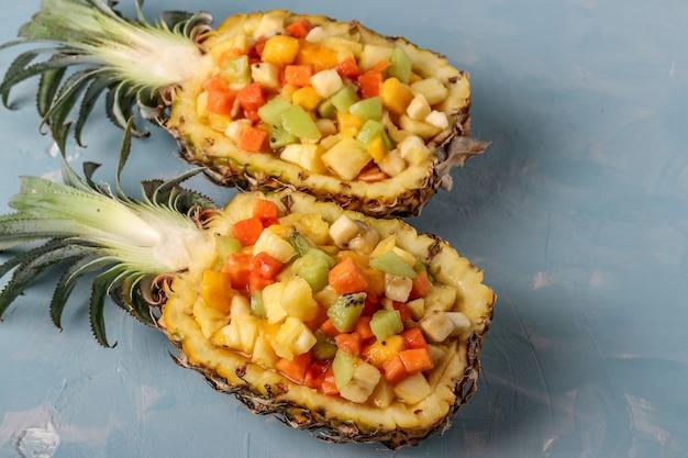 Salada de frutas tropicais em metades de abacaxi em um fundo azul claro, closeup, orientação horizontal