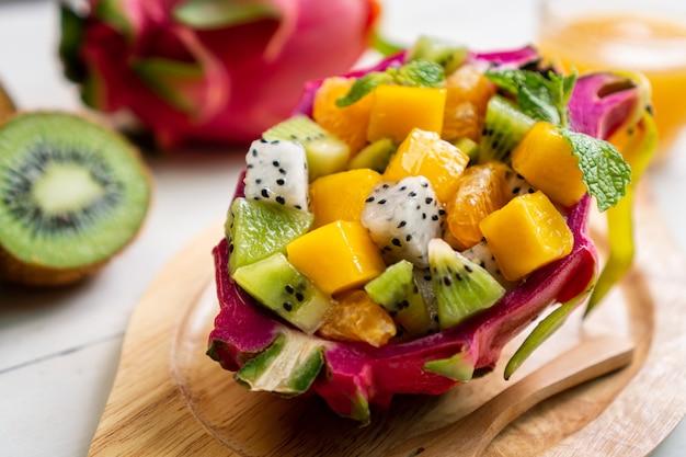 Salada de frutas tropicais servida ao meio de fruta do dragão