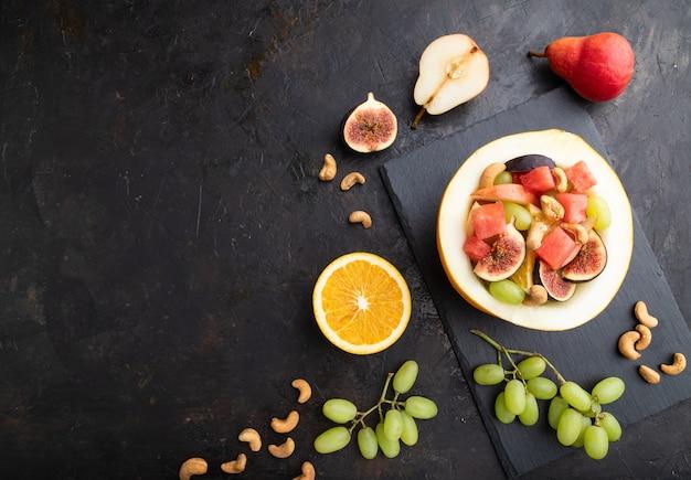 Salada de frutas vegetariana de melancia, uvas, figos, pêra, laranja, caju na placa de ardósia em um fundo preto de concreto. vista superior, configuração plana, copie o espaço.