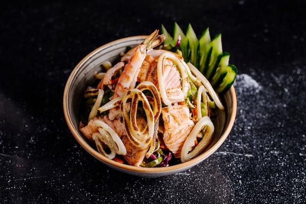 Salada de frutos do mar com fille de salmão, caranguejos e legumes dentro da tigela.