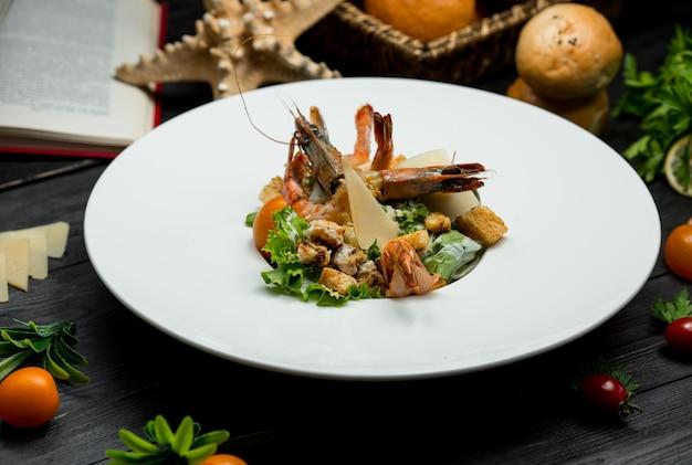 Salada de frutos do mar com parmesão fresco, bolachas, hortaliças, dentro de um prato branco
