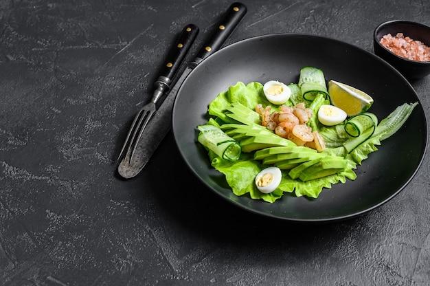 Salada de frutos do mar frescos com camarões grelhados camarões, ovo, abacate e pepino em um prato. fundo preto. vista do topo. copie o espaço.