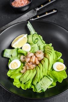 Salada de frutos do mar frescos com camarões grelhados camarões, ovo, abacate e pepino em um prato. vista do topo.