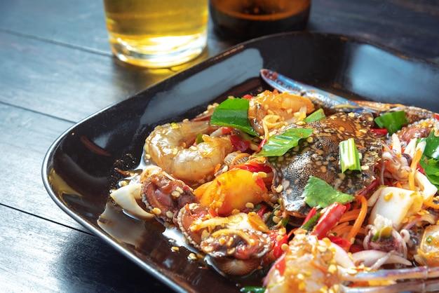 Salada de frutos do mar tailandês e copo de cerveja na mesa preta