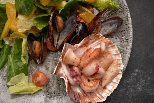 Salada de frutos do mar, tentáculos de polvo, vieiras, camarões tigre, lulas, mexilhões, abacaxi, laranja, mistura de salada, cereja, molho de laranja