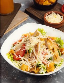 Salada de galinha. frango caesar salad. caesar salad com a galinha grelhada na placa. peito de frango grelhado e salada fresca no prato