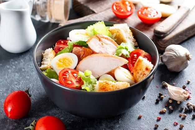 Salada de galinha. salada césar de frango. salada caesar com frango defumado em um prato. peito de frango grelhado e salada fresca no prato