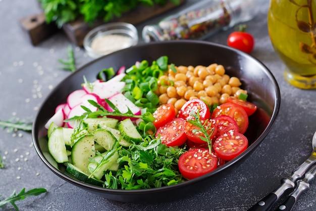 Salada de grão de bico, tomate, pepino, rabanete e verduras. comida dietética. tigela de buda. salada vegana.