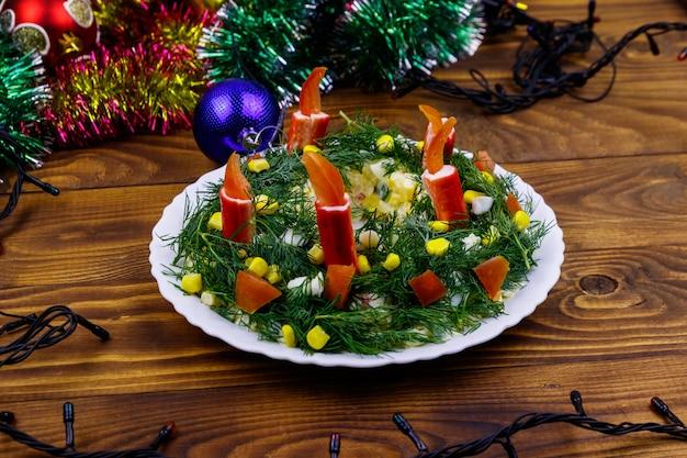 Salada de guirlanda de natal e decorações de natal em uma mesa de madeira