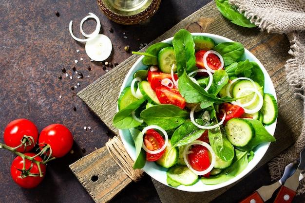 Salada de lanche vitaminado com vegetais frescos e espinafre em uma mesa de pedra escura ou de concreto