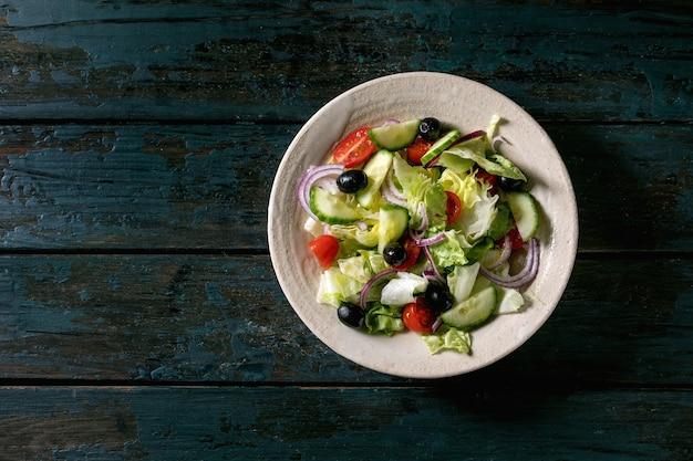 Salada de legumes clássica com tomate, pepino, cebola, folhas de salada e azeitonas pretas em prato de cerâmica branca. fundo de madeira escuro. postura plana, copie o espaço