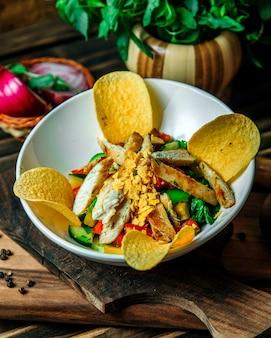 Salada de legumes coberta com fatias de frango e batatas fritas