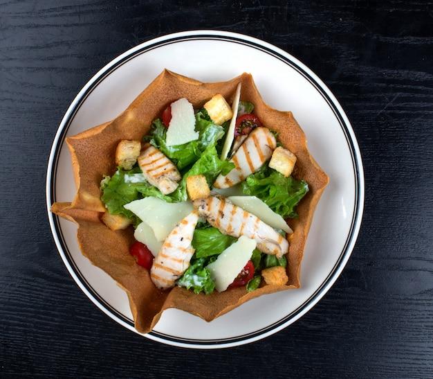 Salada de legumes coberta com peito de frango e bolachas