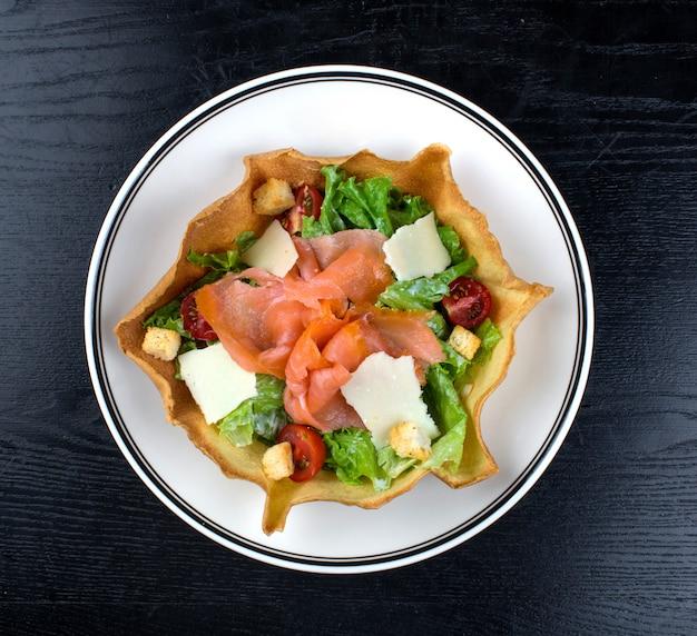 Salada de legumes coberta com salmão defumado e queijo