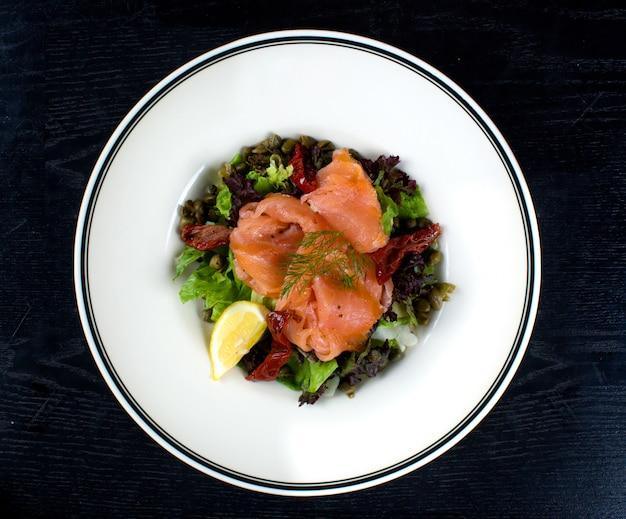 Salada de legumes coberta com salmão defumado