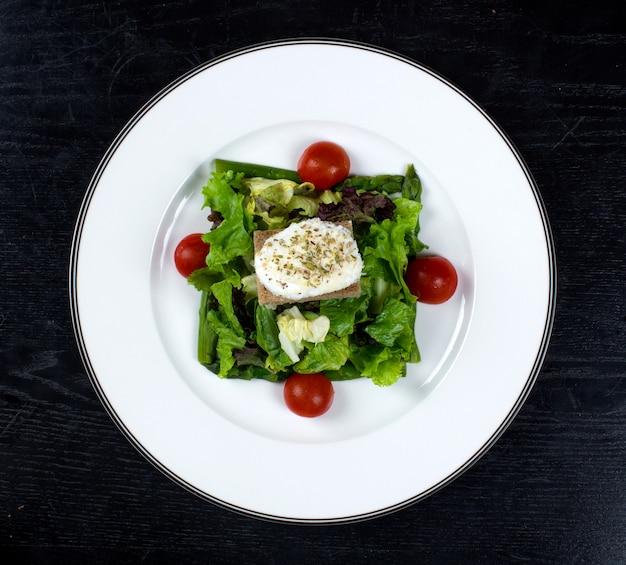 Salada de legumes coberta com tomate e creme