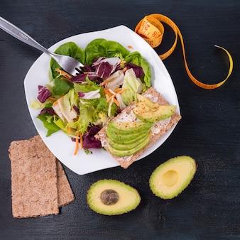 Salada de legumes com abacate no pão torrado