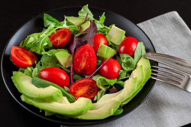 Salada de legumes com abacate, tomate cereja, rúcula e espinafre em uma placa preta sobre uma superfície escura.