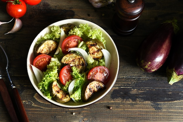 Salada de legumes com alface, tomate e berinjelas grelhadas na mesa da cozinha.