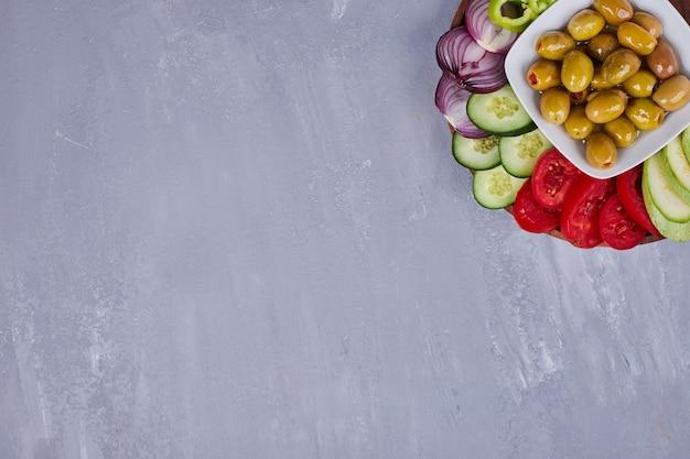 Salada de legumes com alimentos fatiados e picados e azeitonas marinadas.
