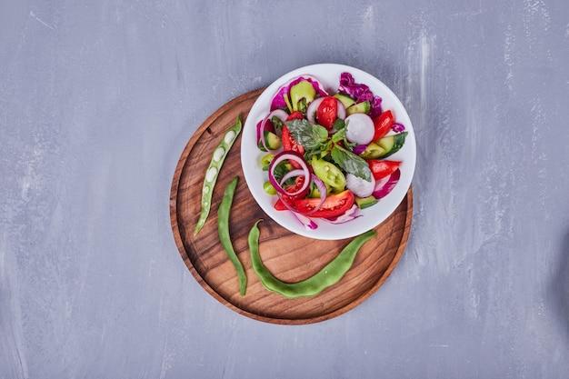 Salada de legumes com alimentos fatiados e picados em prato branco dentro da bandeja de madeira.
