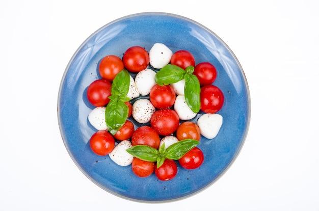 Salada de legumes com bolas de mussarela no prato, fundo branco. foto do estúdio.