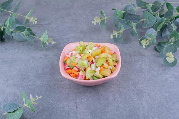 Salada de legumes com comidas da estação em prato de cerâmica