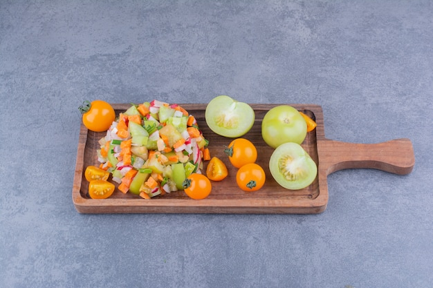 Salada de legumes com comidas da estação em prato de madeira