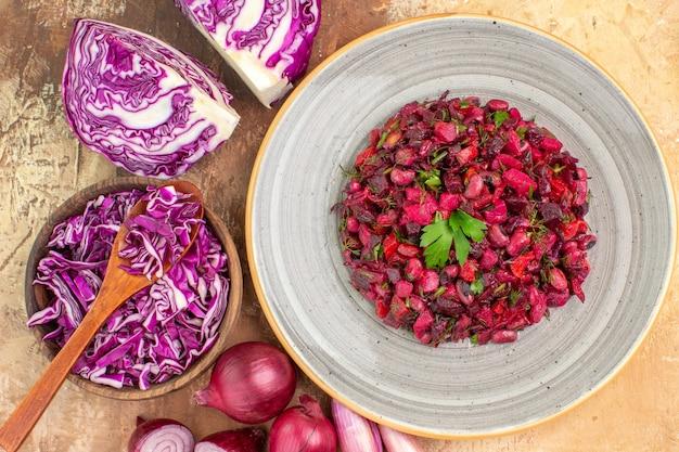 Salada de legumes com folhas de salsa por cima em um prato de cerâmica com repolho roxo picado e cebola em um fundo de madeira.