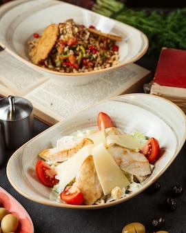 Salada de legumes com frango e coberto com tomate e queijo