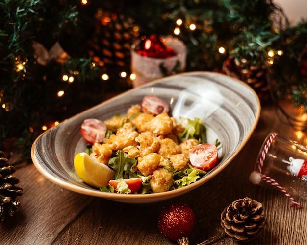 Salada de legumes com pedaços de frango frito crocante