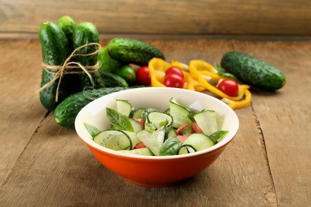 Salada de legumes com pepino na mesa de madeira