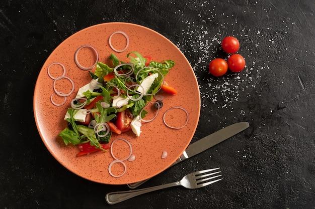 Salada de legumes com pimenta vermelha, rúcula, pepino fresco, tomate, cebola e queijo tofu. um prato de salada vegetariana fresca em uma mesa preta. vista do topo.