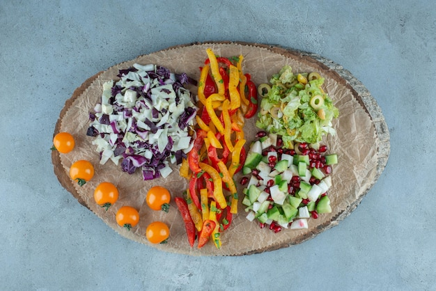 Salada de legumes com repolho branco e roxo picado e acompanhamentos.