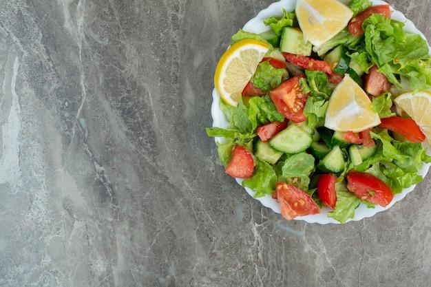 Salada de legumes com rodelas de limão na chapa branca. foto de alta qualidade